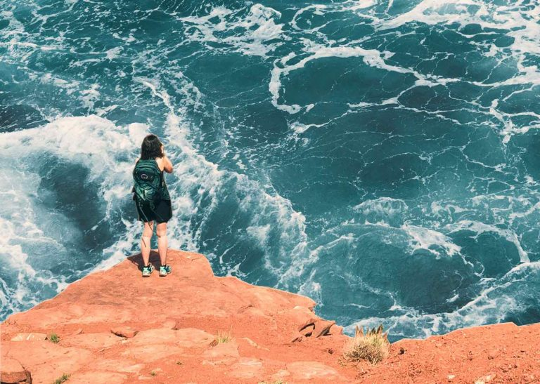 Collaged photos of a person standing on a cliff taking a photo of the water below