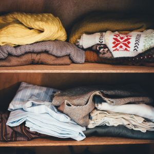 Photo of wooden shelves with multicolored knit sweaters on them