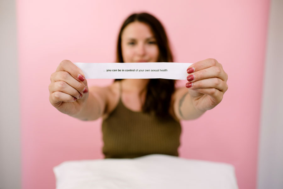Photo of a person holding a piece of paper that says 'you can be in control of your own sexual health' in front of a pink backdrop as part of Trillium's Pillow Talk campaign
