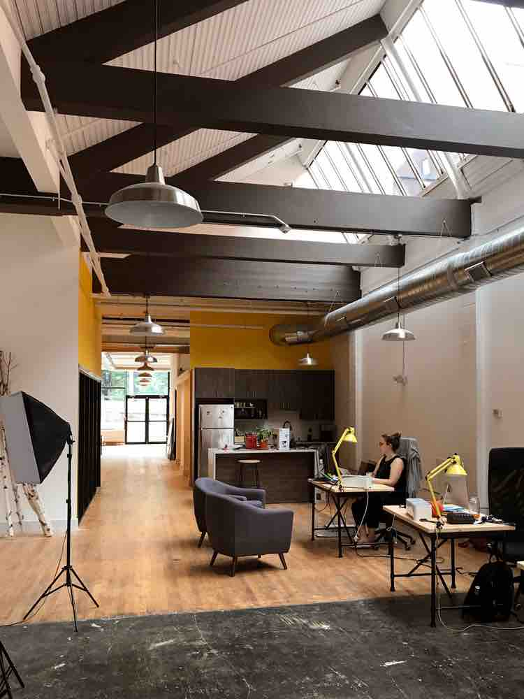 Interior of TGW Studio office with a person working at a desk, desk setups, photography set up, and a kitchen