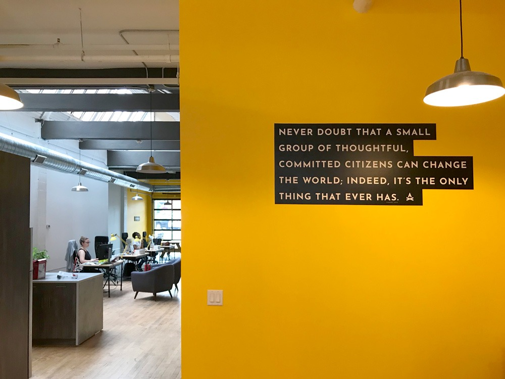 "Interior of TGW Studio office with people at desks and a wall that has a quote on it that says 'Never Doubt That A Small Group Of Thoughtful, Committed Citizens Can Change The World; Indeed, It's The Only Thing That Ever Has.' as part of the ""We Moved"" post"