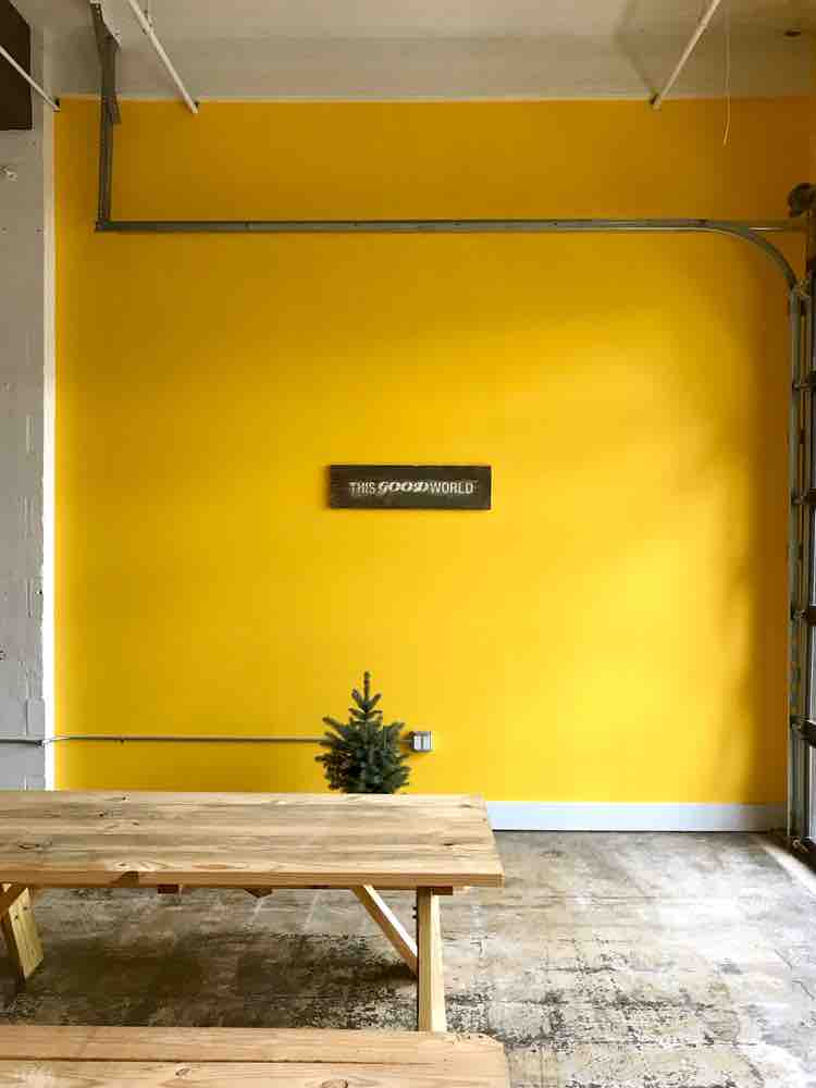 "Interior of TGW Studio office depicting a yellow wall with a sign that says 'This Good World', a picnic table, and a small green tree as part of the ""We Moved"" post"