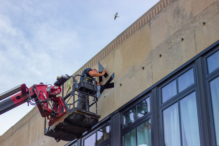 Person installing TGW Studio lettering on the exterior of the building. New-new