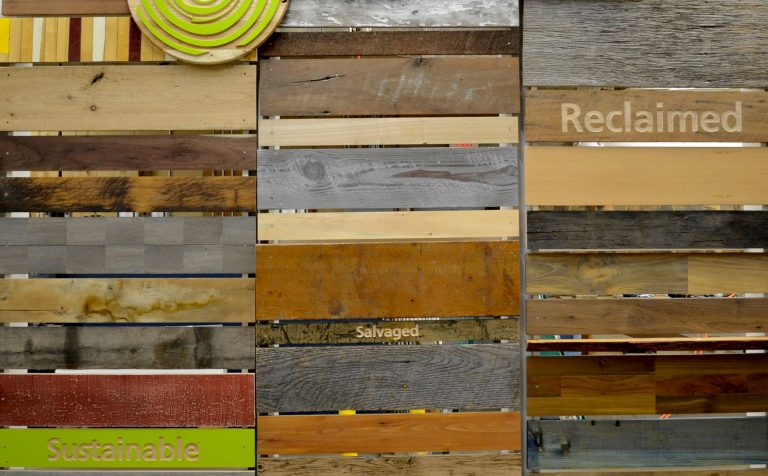 Photo of Pioneer Millworks multicolor wood samples with text that says 'sustainable, salvaged, and reclaimed'