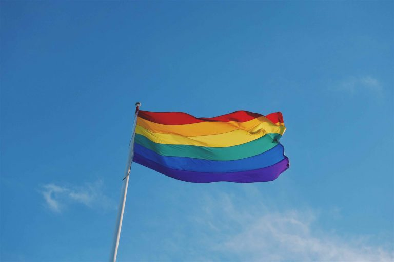 Photo of a rainbow pride flag on a flag pole