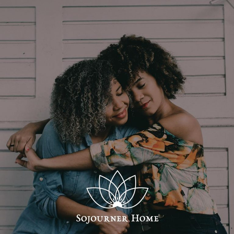 Photo of two women hugging in front of a white wall with text overlaid that says 'Sojourner Home'
