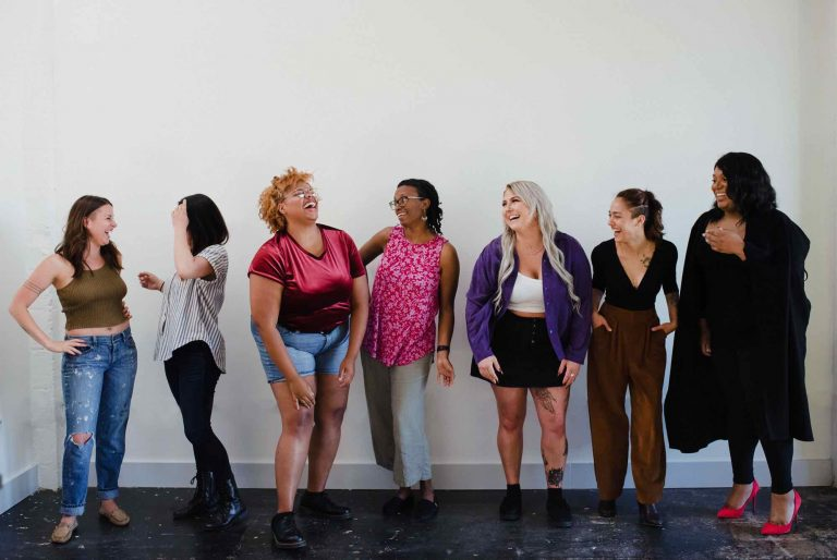 Photo of seven women laughing and smiling in front of a white wall as part of Trillium's Prep campaign