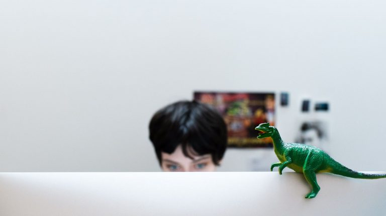 CB, our Creative Lead, sit behind her computer. A toy dinosaur is sitting atop the monitor