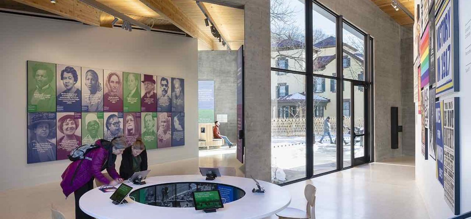 Photo of the interior of the Equal Rights Heritage Center which shows two people interacting with a digital exhibit on an iPad. Behind them is a wall of portraits of key figures in U.S. history