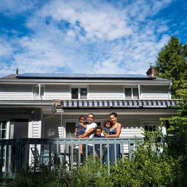 Photo of a man, woman, and three children on a blue porch in front of their white house with solar panels on it, surrounded by green bushes and trees depicting social responsibility