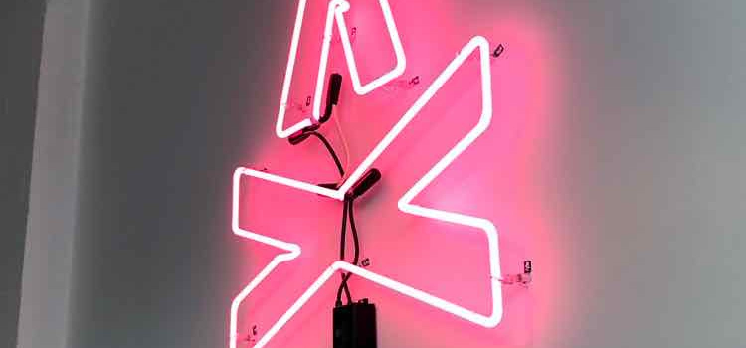 Photo of the TGW Studio neon sign, which features the TGW logo, a graphic representation of a campfire
