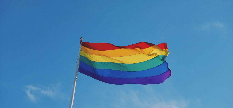 Photo of a rainbow pride flag on a flag pole