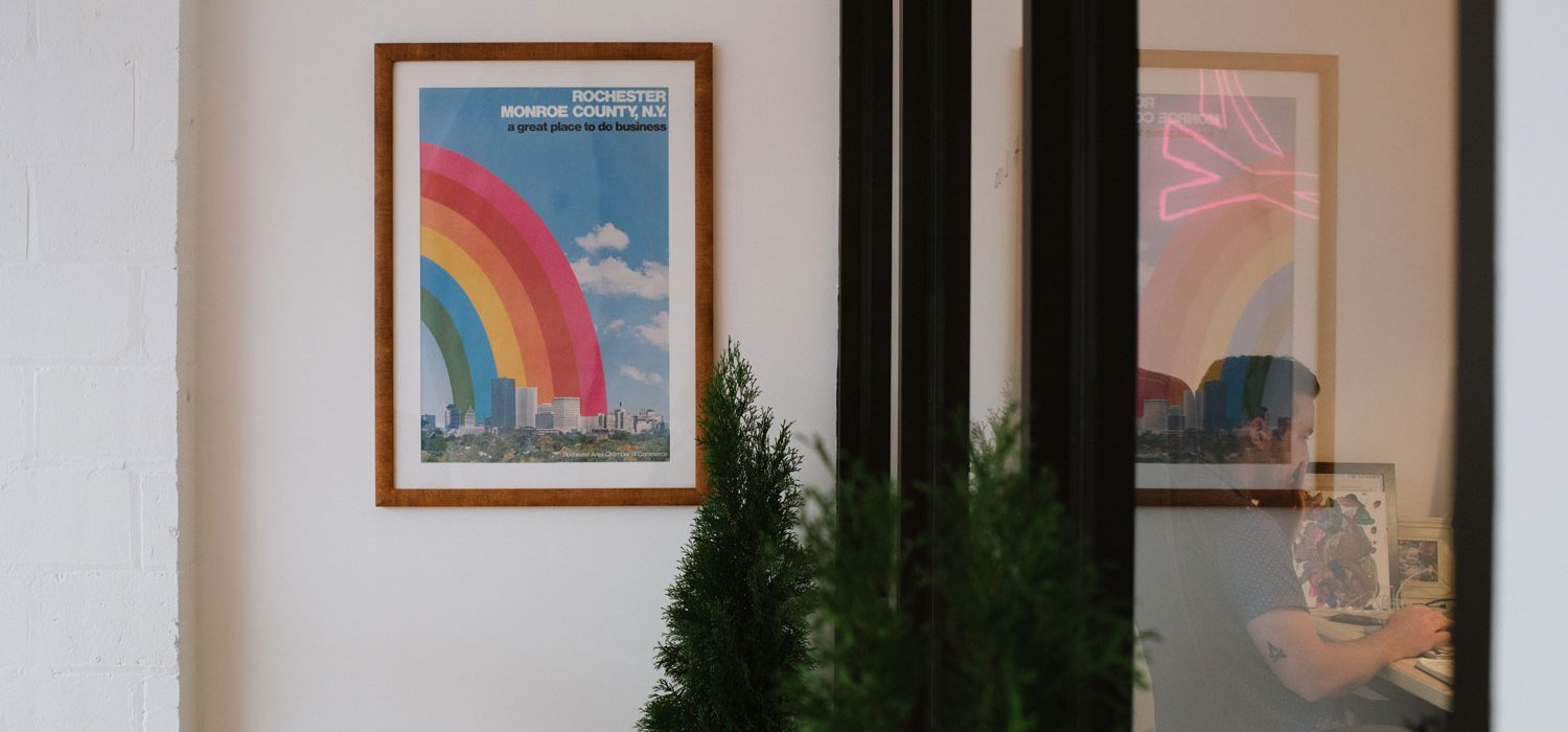 Photo of the interior of TGW offices with a green tree, office windows, and a poster that has a rainbow over Rochester with the text 'Rochester Monroe County, NY, a great place to do business'