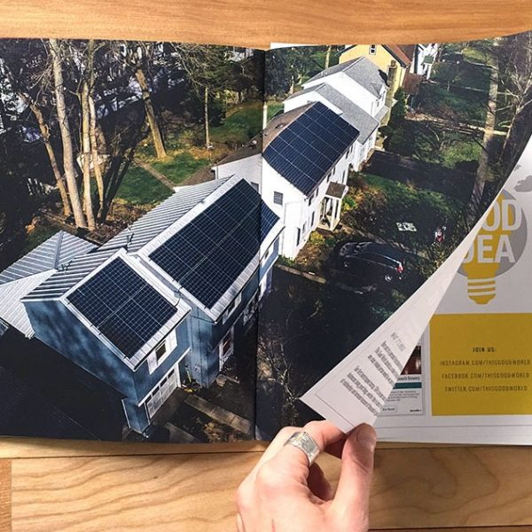 Person turning the page of a booklet with a spread that shows a neighborhood with solar panels depicting social responsibility